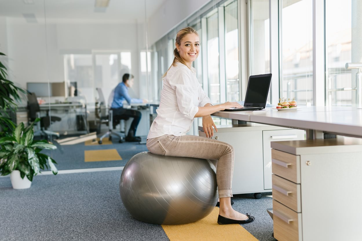 Business_woman_sitting_on_pilates_ball.jpg